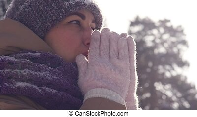 Portrait of a young woman outdoors who is breathing in her arms to keep warm while walking in the winter park
