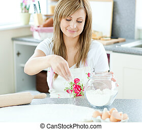 Portrait of a young woman preparing a cake in the kitchen