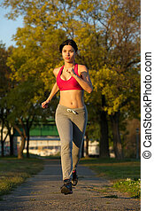 Portrait of a young woman running in the park