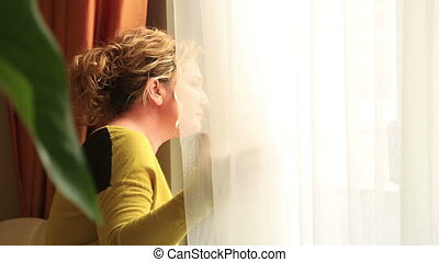 Portrait of a young woman sitting alone looking out window