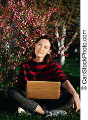 Portrait of a young woman sitting cross-legged on a lawn under a blossoming bush
