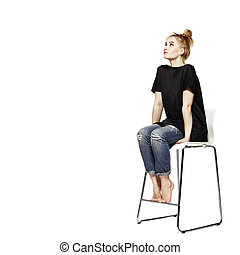Portrait of a young woman sitting on modern chair