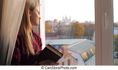 Portrait of a young woman that reads a book near the window