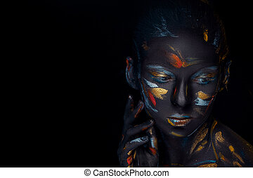 Portrait of a young woman who is posing covered with black...