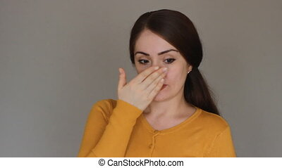 Portrait of a young woman who scratches the nose. Allergic reaction of the nose. Rhinitis, sinusitis