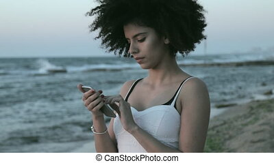 portrait of a young woman with a frizzy afro hairstyle texting