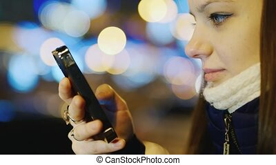 Portrait of a young woman with a mobile phone in the night city