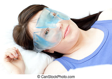 Portrait of a young woman with an eye gel mask