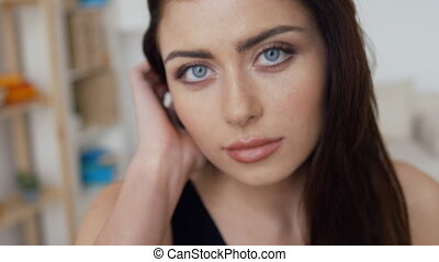 Portrait of a young woman with blue eyes touching her beautiful dark hair, close up