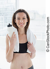 Portrait of a young woman with towel around neck holding water bottle in fitness studio