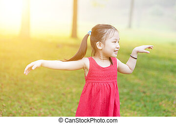 Asian child dancing outdoors.