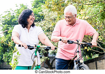 Portrait of active senior couple standing on bicycles