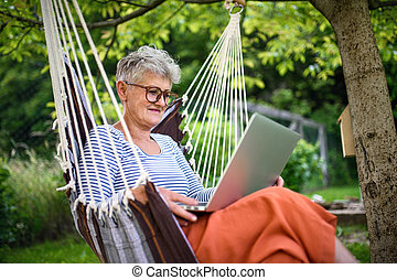 Portrait of active senior woman with laptop working outdoors in garden, home office concept.