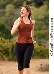 active young woman running outside in nature