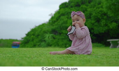 Portrait of adorable 6-months baby girl who is chewing and sucking black smartphone on outdoor