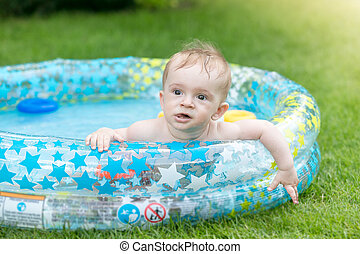 Portrait of adorable baby boy lying in inflatable swimming pool at house backyard