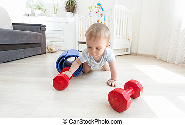 Portrait of adorable baby exercising with dumbbells on floor at living room