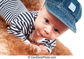 Portrait of adorable baby in cap lying on fur