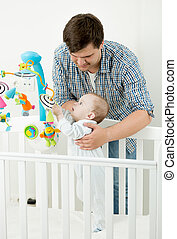Portrait of adorable baby playing in cot with his father