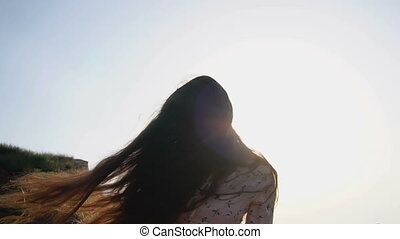 portrait of Adorable Caucasian Brunette girl in Light Pink Dress Play with Her Long Beautiful Hair at Sunrise Time.
