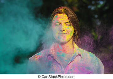 Portrait of adorable caucasian girl posing in a cloud of a pink and blue dry paint at Holi Festival