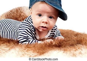 Portrait of adorable child in hat lying on fur