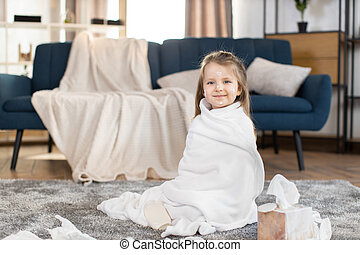 Portrait of adorable cute little 3 years old girl, sitiing on the floor at cozy room at home, wrapped in big white towel after bath, having fun with drops of body milk on face. Baby care and hygiene