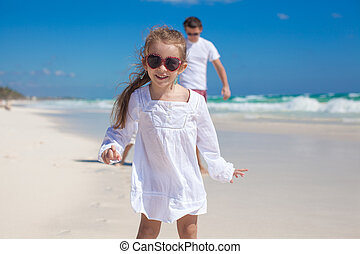 Portrait of adorable girl and his father with little sister in the background at tropical beach