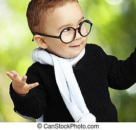 portrait of adorable kid wearing glasses gesturing doubt against