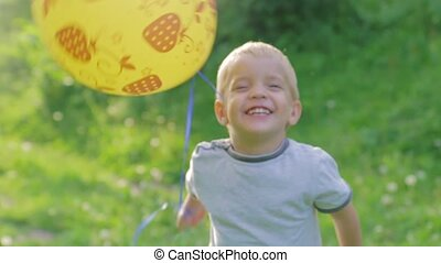 Portrait of adorable little boy laughing and smiling playing with a balloon