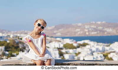 Portrait of adorable little girl background Mykonos town in Europe