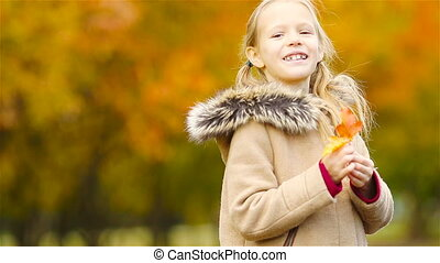 Portrait of adorable little girl outdoors at beautiful warm...