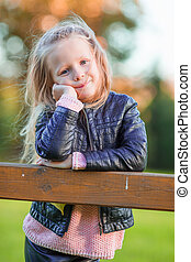 Portrait of adorable little girl outdoors at beautiful autumn day