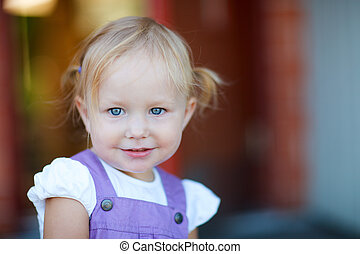 Outdoor portrait of adorable playful 2 years old girl