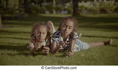 Portrait of adorable sisters lying on green grass - Portrait...
