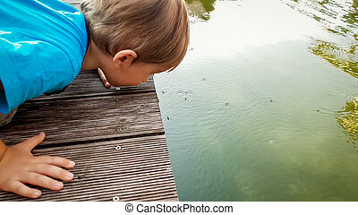 Portrait of adorable toddler boy looking on the lake surface...