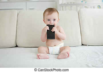 Portrait of adorable toddler boy sitting on sofa and biting smartphone