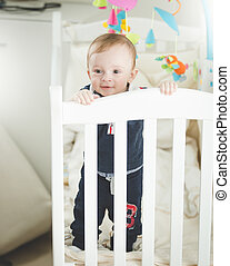 Portrait of adroable 1 year old baby boy standing in white wooden crib
