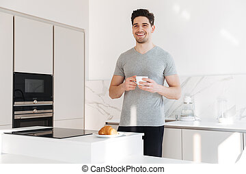 Portrait of adult man in casual clothes smiling and holding cup of coffee, while having breakfast in apartment