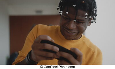 Portrait of african american black man playing games on the smartphone and winning. High quality 4k footage
