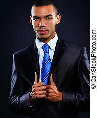 Portrait of African American businessman with arms together isolated over dark background