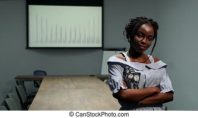 Portrait of African American businessman woman standing in office in front of a big table and graphs on the screen looking at the camera