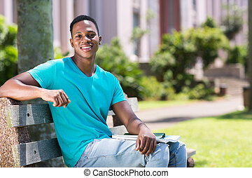 african american college boy sitting on bench