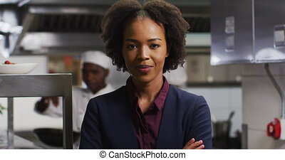 Portrait of african american female manager with arms crossed in restaurant kitchen