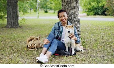 Portrait of African American girl loving dog owner sitting...