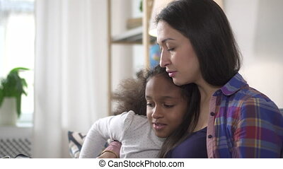 Portrait of african american happy girl from secondary school talking to adult woman in flat who teaching her and helping with homework
