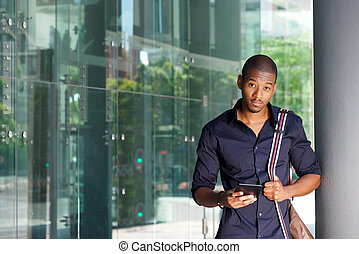 african american male student standing outside with tablet and bag