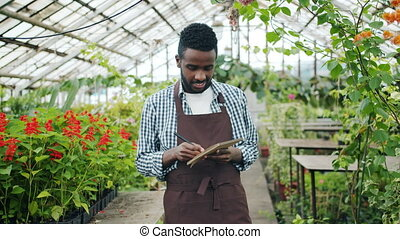 Portrait of African American man writing in notepad looking...