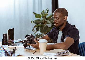 portrait of african american photographer with photo camera