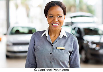 african american saleswoman standing at car dealership